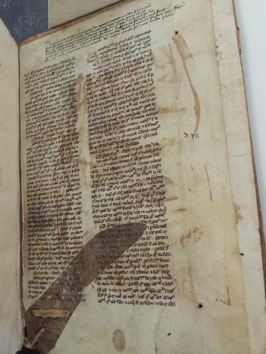 Manuscript leaf covering the inside of the back cover of the book. Torn strip of paper reveals cord threaded into the wooden cover.