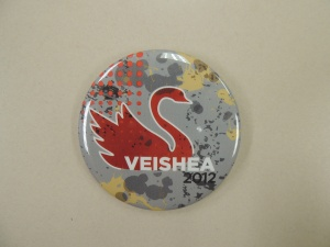 "button gray background with orange swan and orange dots above swan's tail, splashes of dark gray and yellow in background, white text says ""VEISHEA"" then 2012 in black text."