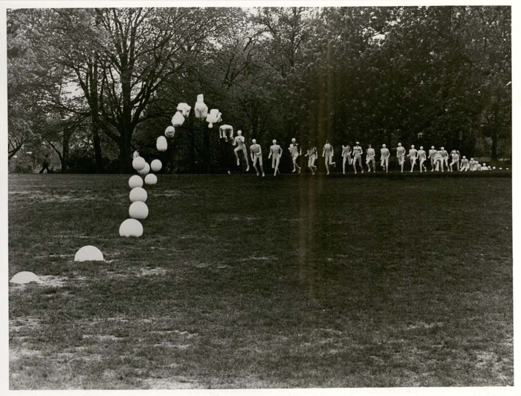 Art installation on lawn, shows human figures in white running than at some point they leap into the air, curl up, and land as balls.