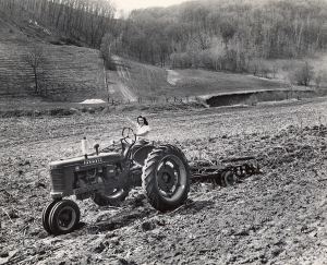black-and-white photograph, young woman on tractor in field.