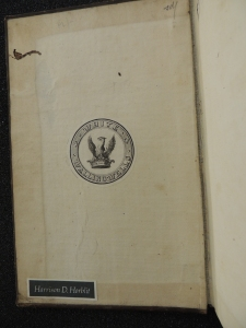Inside front cover of a book showing a bookplate in the center with a coat of arms of a birth of pray with wings extended rising out of a crown surrounded by a ring with the words White Wallingwells. Second bookplate is a simple name in white on gray reading Harrison D. Horblit
