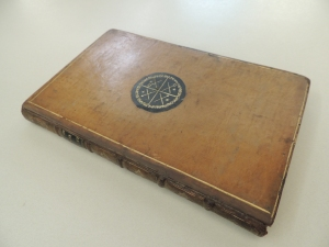 Shows front cover of book bound in leather with a black circle in the center fo the cover with cross-shaped symbols stamped in gold into the circle.