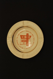 "Photograph of a commemorative ashtray, yellow with rd text and gold border around rim, ""With honor to the past, with vision for the future, 1858 centennial 1958, Iowa State College"""