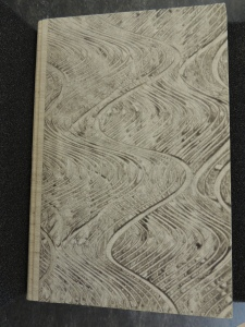 Cover of book covered in paper which has been covered in gray and and a tool has been used to create a wavey pattern in the paint.