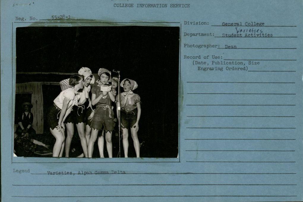 """Photograph of 5 young women around a microphone in costumes of cut jean shorts, bonnets & ropes for belts. On college information service card reads division of General College, Department, Student Activities, Varieties, Photographer """"Dean"""". Underneath the hpotograph is says """"Varieties, Alpah [sic] Gamma Delta."""