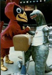 Cy, the Iowa State mascot, a cardinal, is wrestling a dinosaur over a pommel horse.