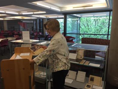 Woman standing in front of 2 exhibit cases and a book cart, she is installing new exhibit. Background has tables/chairs for studying and windows of outside view of trees.