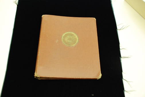 "3-ring binder front cover. Medium brown covers, spine and lining. Silver colored metal binder. Balck stiffeners. Seal has gold on it. INSCRIPTION: ""Iowa State College of Agriculture and Mechanic Arts; Science with Practice"""