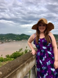"Young woman in purple dress with straw hat, view behind her is coast:; ""cristo de la misericordia"" (Christ of the Merdy) on the coast of San Juan del Sur in Nicaragua."