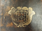 Coat of arms stamped in gold leaf on brown leather.