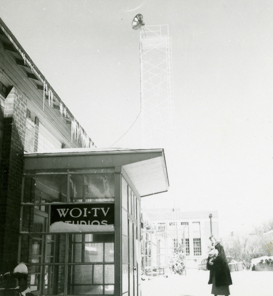 This photograph shows Exhibit Hall at Iowa State University in 1953. The signal tower is in the background. A sign on the door says: WOI-TV Studios. A women is walking to the door. Snow is on the ground.