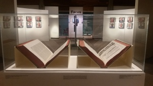 Two books open for display in a glass museum case.
