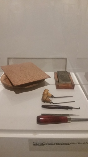 Exhibit case filled with burins and other engraving tools and an engraved copper plate.