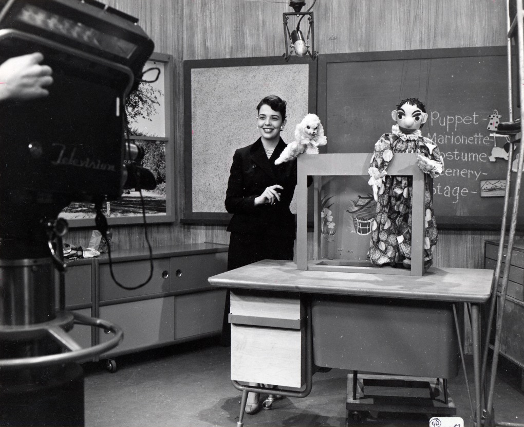 Black-and-white photograph of woman with ahir in updo, wearing dark dress, holding a puppet on her left hand (Betty Lou [McVay] Varnum) on the set of The Magic Window on WOI-TV in 1957. Betty Lou is standing next to a desk and there is another puppet on the desk.