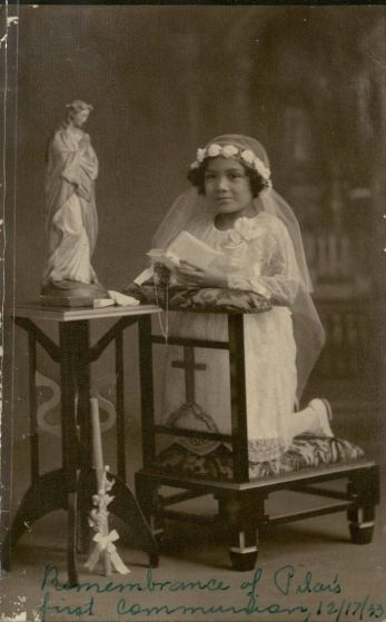 Image of young filipino girl kneeling in front of Virgin Mary in white communion dress and veil with an open book (prayers or the bible?) in front of her. Written in green at bottom of photograph: Remembrance of Pilar's first communion, 12/17/33.""