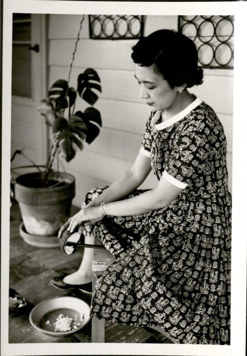 Photogaph of Pilar Garcia shaving coconut sitting on a Kudkuran ng niyog, also known as a coconut grater. She's wearing a dress and there is a plant in the left corner. She's sitting outside.
