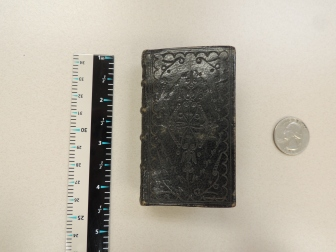 Pictured from left to right: vertical ruler (for scale), book, and quarter (for scale). Book measures a little over 3 inches.