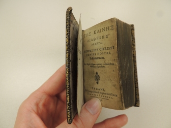 Handing holding a 3-inch tall book open to the title page.