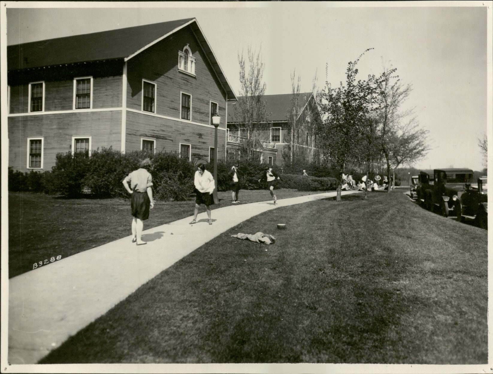 Young women playinig hopscotch in school uniforms on sidewalk in what looks like a neighborhood. Some students in distance are sitting down and cars are parked on the curb. Black-and-white photo. No date.