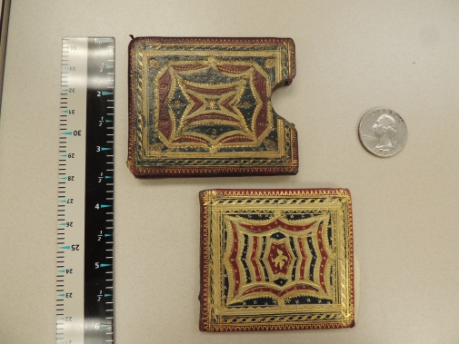 Pictured are a 2 1/2 inch tall book decorated in red and blue leather inlays and gold leaf in a similarly decorated slipcase. Shown for scale: a ruler and a quarter.