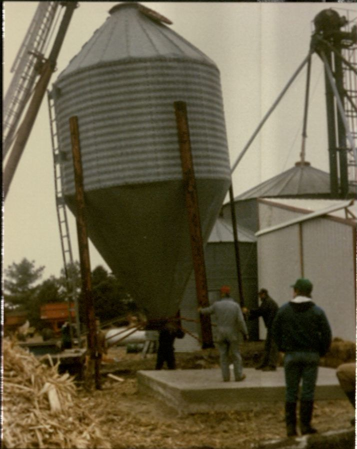 Color snapshot of a crane setting a small grain bin up on a cement platform. People are standing around and helping guide it into place.