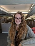 Photograph of white female student, long hair with glasses, close-up in a library office setting (cubicle & book shelves filled with books visible in the background).