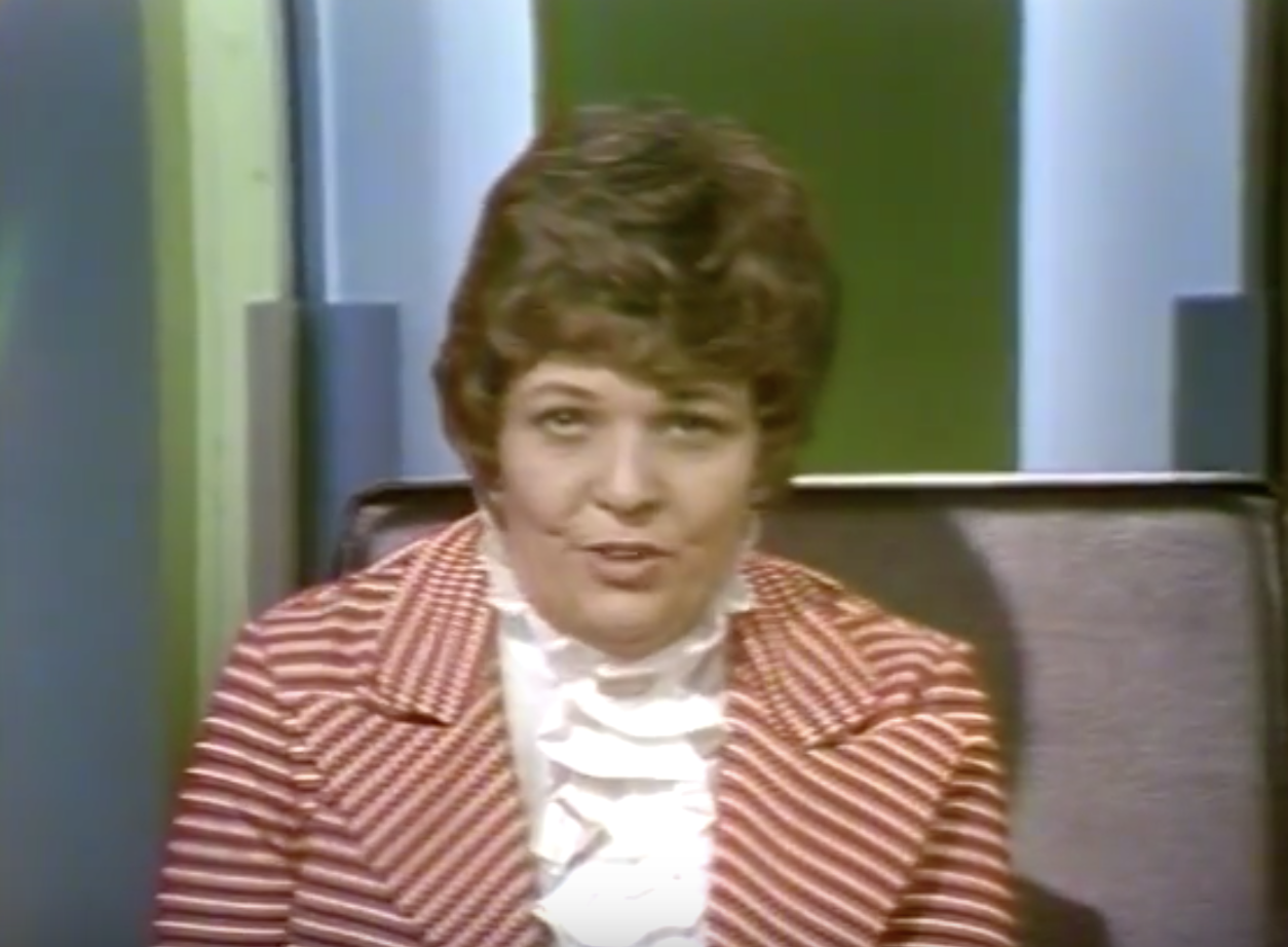 Headshot of Betty Lou Varnum. Screenshot from the video entitled Dimension 5: Gay People Alliance, time 0:30. Varnum is introducing the segment. Follow URL in the caption to see this moment in the video.