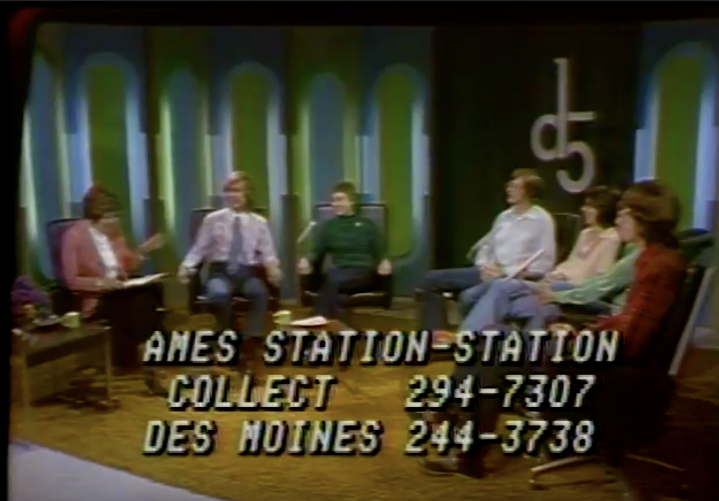 Screenshot from the video entitled Dimension 5: Gay People Alliance, time 1:39. Carolyn Czerna, Karen Moore, Kay Scott, Connie Tanzo, Steve Court, Jim Osler, David Windom, and Dennis Brumm being introduced. Follow the URL in the caption to see this moment in the video.