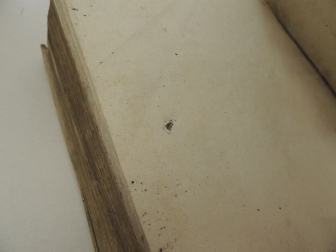 Blank flyleaf showing a hole from a knife.
