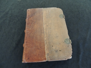 Cover of book shows leather covering one half of the book going around the spine. The other half is an exposed wood board with clasps holding it closed. The wood board has a number of small holes about a milimeter in diamter..