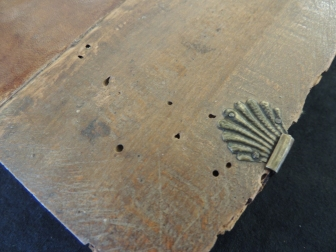 More 1 milimeter sized holes drilled into the wooden cover of book.