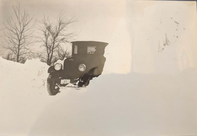Black-and-white photograph of car driven on snowy road, snow banks in foreground, trees in background, date is 1936.