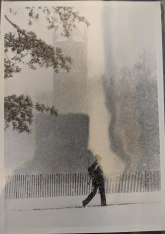 Black-and-white photograph of person wearing beanie and backpack walking in front of looks like Iowa State University's Campanile, it is snowing enough that background is fuzzy, dated 1979.