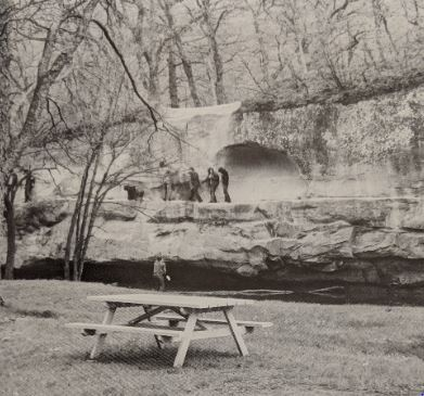 Three people standing on a limestone cliff over a river in Ledges State Park while a fourth member watches from below.