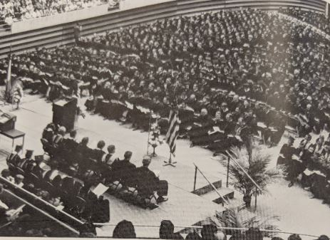 Students in their caps and gowns sitting in folding chairs at their graduation ceremony.