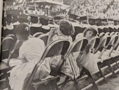Three children wearing dresses sitting on folder chairs in the back row of the graduation ceremony in 1964.