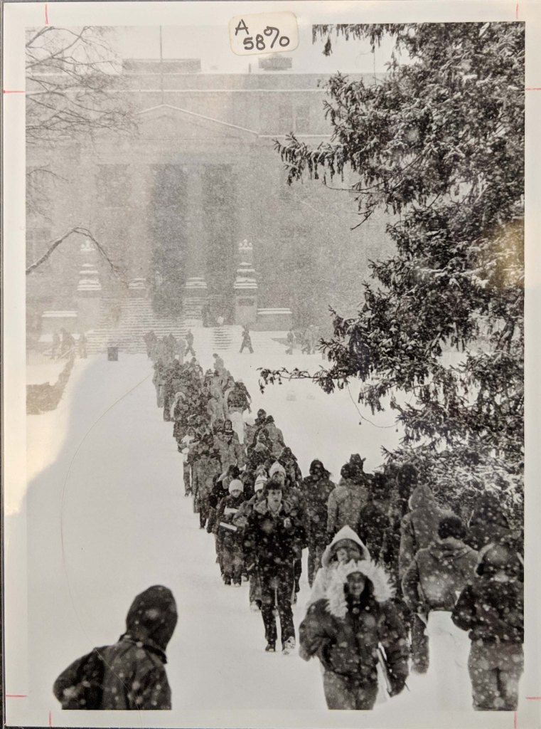 A large group of students walking along the sidewalk on central campus that runs from Curtiss Hall to Beardshear Hall in a heavy snow fall, 1979.
