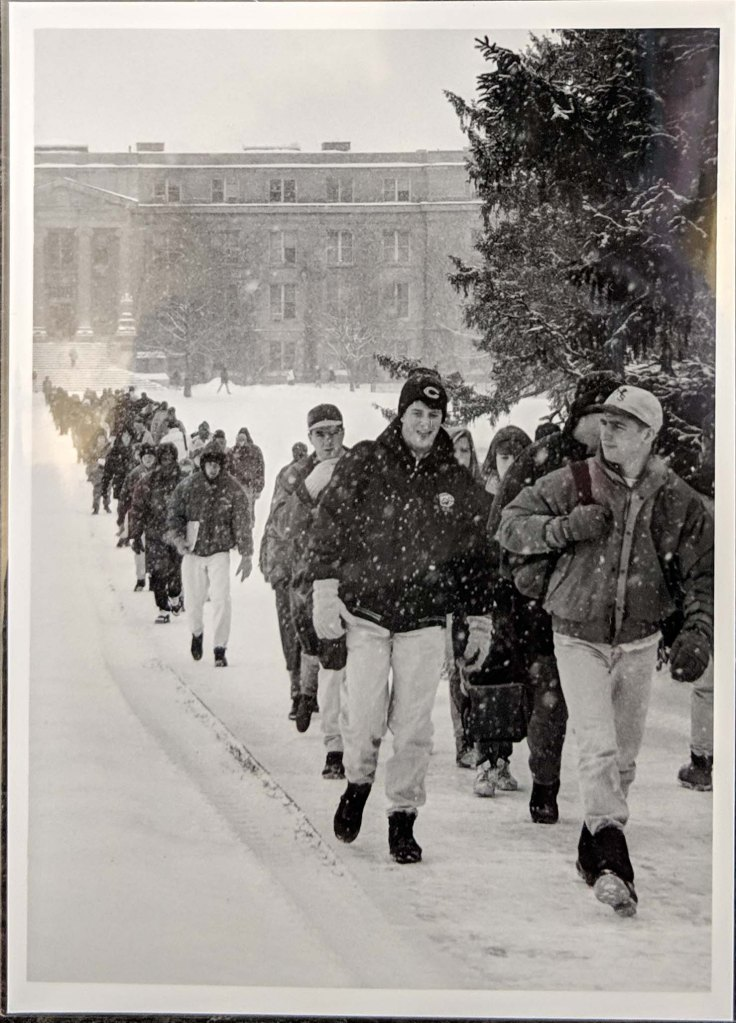 A large group of students walking along the sidewalk on central campus that runs from Curtiss Hall to Beardshear Hall in the snow, 1994.
