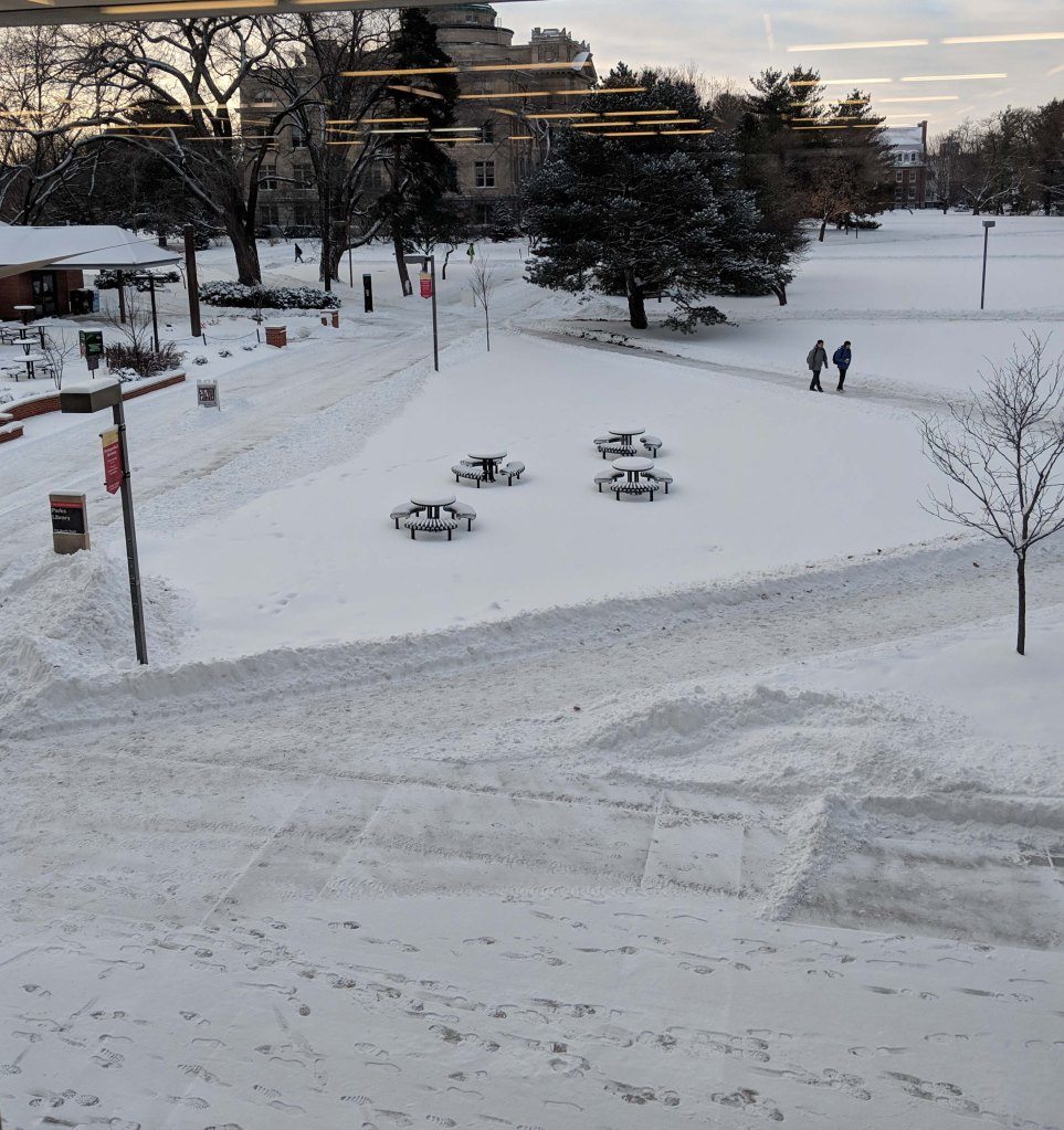 View from the second floor windows of Parks library looking out over the snow covered free speech area, Beardshear Hall is in the background.