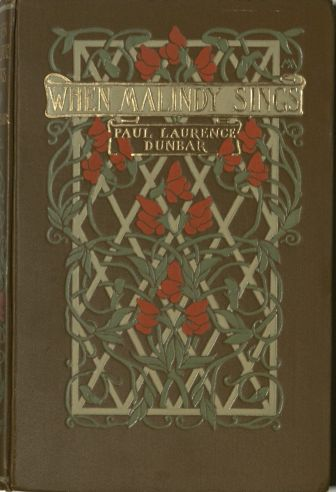 Brown book cloth stamped with a square design of repeating diamond shapes with red flowers on green vines entwined around the diamonds.