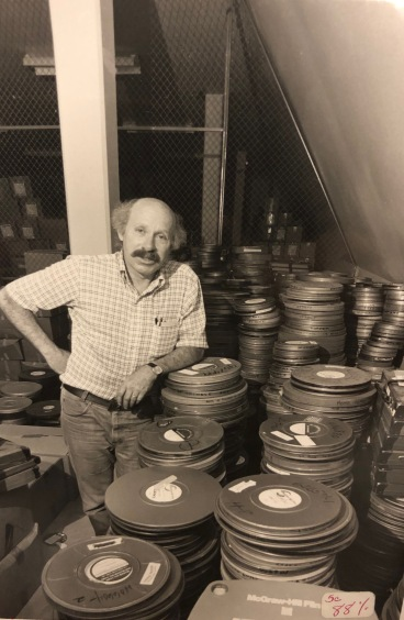 Stanley Yates, standing amidst film canisters from the American Archives of the Factual Film, 1981 (University Photographs, box 2053).