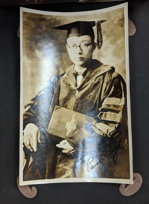 Photo album page of student Fan-Chi Kung, holding a black and white photo of a student posing in their cap and gown after graduation.