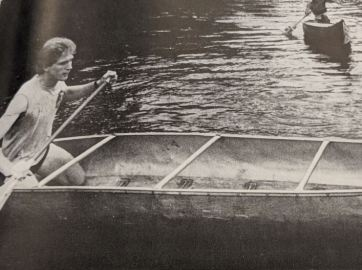 Student rowing a canoe down a body of water.
