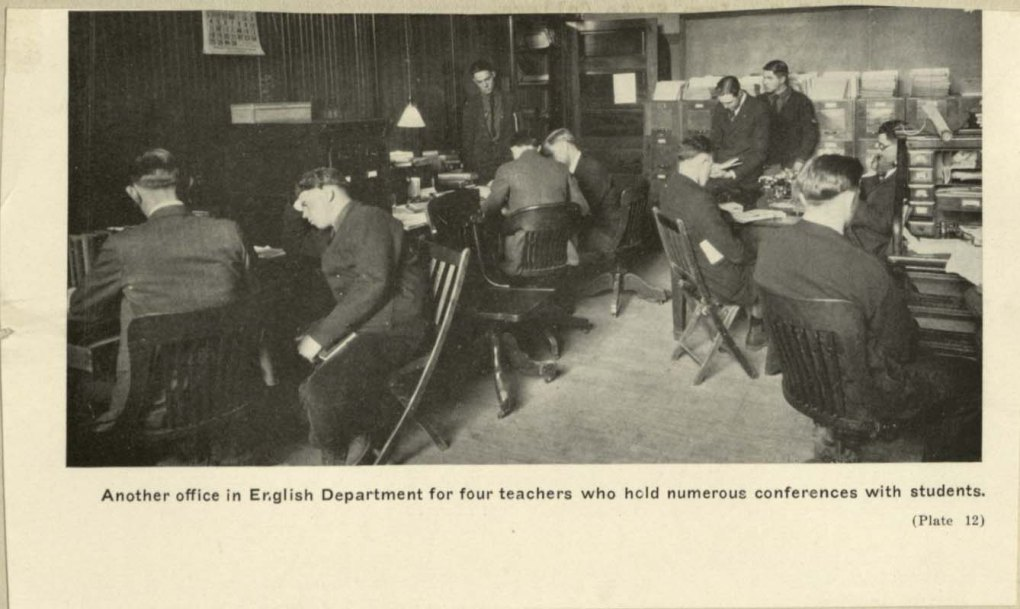 Black and white photo of the Iowa State University English department professors meeting with their students in a shared office space in 1923.