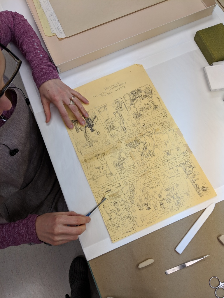 Overhead photo of collections conservator Sonya Barron working on a drawing from a comic from the Underground Comix Collection.