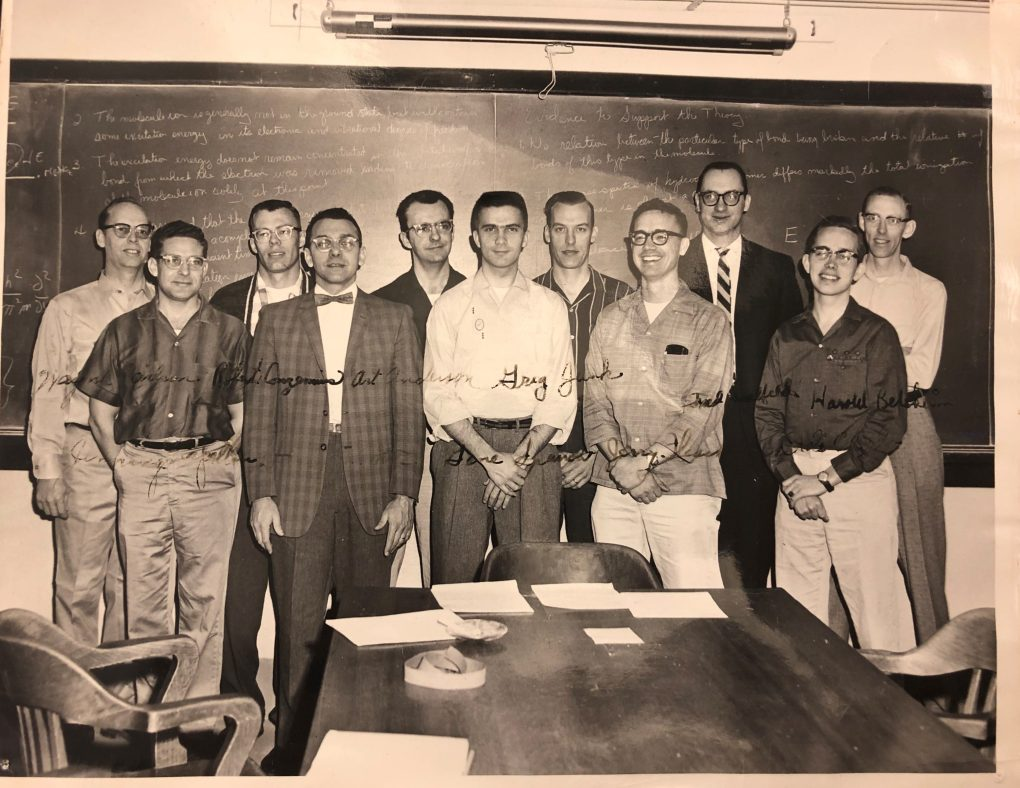 Group of faculty and students in front of a chalkboard.