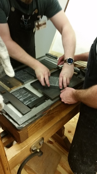 One person holds onto a page of type and transfers it from metal tray, while second person steadies the tray.