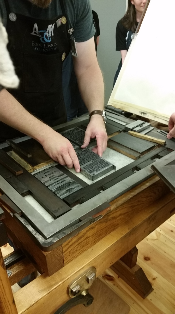 Person holds the page of type in place, moving it as a whole into the correct position.