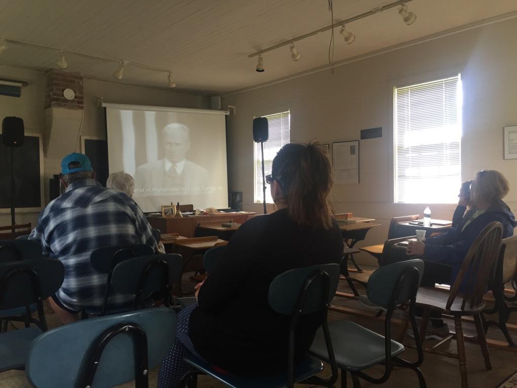 People viewing film screening inside historical one room school house.