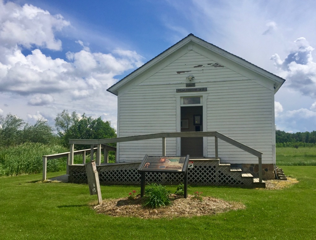 Exterior shot of one room school house, front, on a farm.